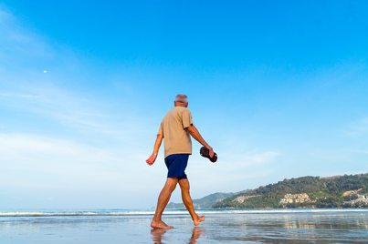 Senior Walking On Beach