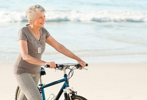 A happy woman with her PAX mobile medical alert on the beach with her bike