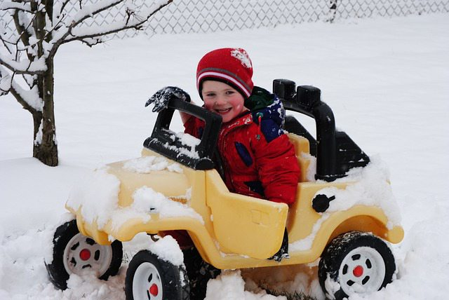 Child driving toy car in snow