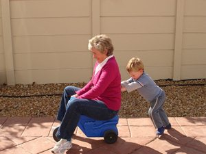 Child pushing grandma on plastic toy car.
