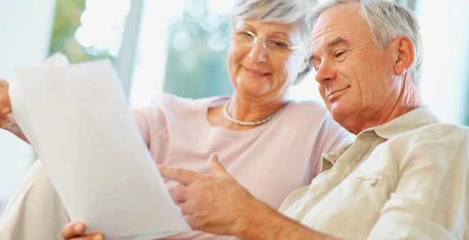 elderly couple smiling at a paper. alert1 medical alert system