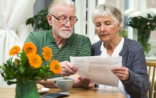 elderlyCouple reading papers. alert1 mediccal alert systems