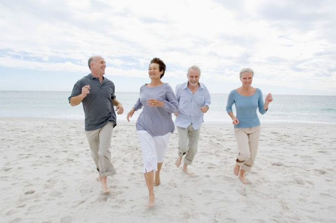 Four elders running on the beach. alert1 medical alert system