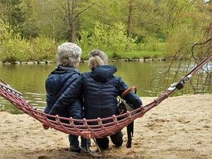 Two people sitting on a swing facing the lake