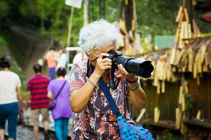 A woman taking a picture with her DSLR camera