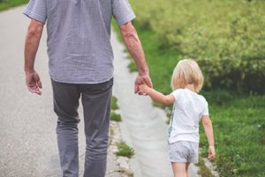 grandpa walking with granddaughter hand in hand