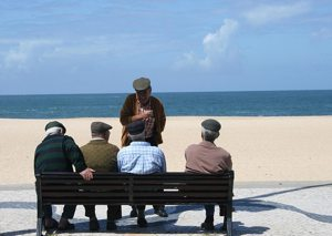 5 old men sitting on bench by beach