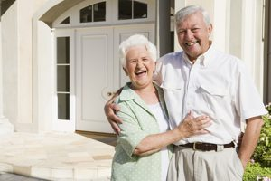 Happy senior couple outside their beautiful home