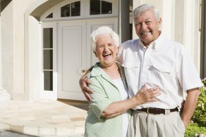 old couple laughing in front of house