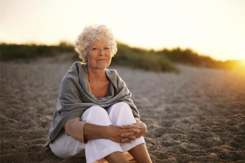 Senior Sitting on Beach Sunset