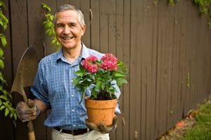 man with potted plant, gardening outdoors with mobile medical alert