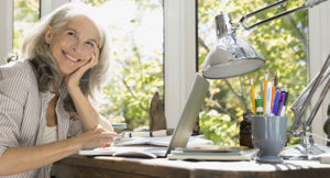 Woman smiling in her home office.