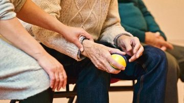 senior hand using exercise ball