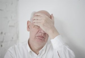 Senior Man Covering Face With Hand