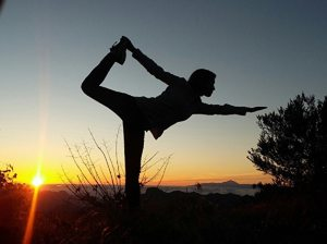 yoga girl stretching outdoors with mobile medical alert